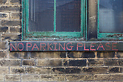 Against the blackened brick after decades of industrial use, the polite words No Parking Please have been painted on the sill of fading green window frames in a quiet street off Lumb Lane near Bradford city centre, Yorkshire.