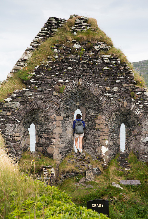 Hiker looking out from ruins of church on Abbey Island, County Kerry, Ireland