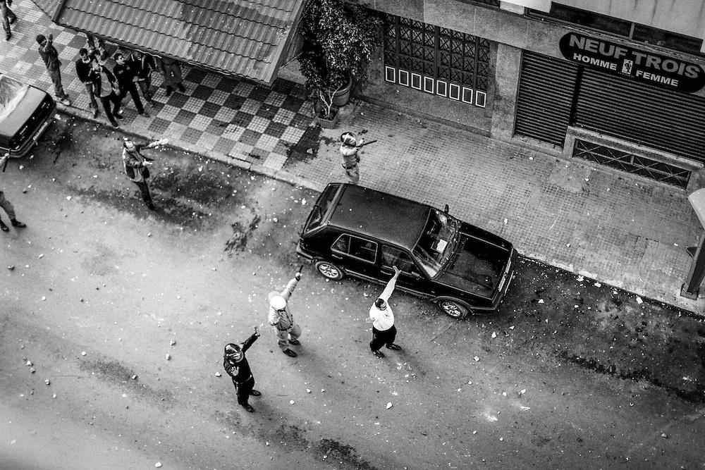 198 / Unruhen in Tanger: AFRIKA, MAR, MAROKKO, TANGER, 20.02.2011: Konfrontation mit der Polizei. Tausende Menschen demonstrieren in Tanger und in ganz Marokko für demokratische Reformen  zum Tag des Stolzes. Sie verlangen unter anderem den Ruecktritt der Regierung, die Aufloesung des Parlaments und eine Verfassungsreform zur Einschraenkung der Macht des Koenigs Mohammed VI. Marokko ist offiziell eine konstitutionelle Monarchie mit einem gewählten Parlament. Allerdings gibt die Verfassung dem König weitreichende Befugnisse, etwa zur Aufloesung des Parlaments und der Ausrufung des Ausnahmezustands. Zudem hat der Koenig entscheidenden Einfluss auf die Ernennung von Regierungsmitgliedern inklusive des Ministerpraesidenten. Die Bewegung des 20. Februar entstand an diesem Tag und fuehrt seitdem die Protestbewegungen im Lande. - Marco del Pra / imagetrust - Stichworte: Afrika, Marokko, Maghreb, Maroc, Tanger, Koenigreich, Koenig, Mohammed VI, Islam, islamisch, Muslim, muslimisch, Arabisch, Berber,  Schwarz, Weiss, Reformen, Tag des Stolzes, Krawall, Pluenderung, pluendern, Proteste, Demonstranten, Demonstration, Demo, Polizei, Gewalt, Strassenschlacht, Steine, Stein, Demokratie, Politik, Monarchie, Monarch, Mohammed VI, Revolution, Revolte, Parlamant, Ausnahmezustand, Regierung, 20fev, 20 Februar, Bewegung, Wuerde, Konfrontation, Konflikt,