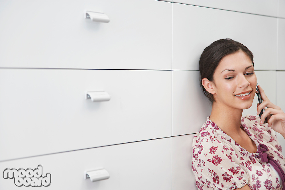 Young woman leaning on cabinet using mobile phone