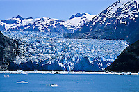 The blue ice of South Sawyer Glacier, a tidewater glacier of the Coast Mountains flows into the water of Tracy Arm, Alaska.