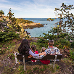 A couple and their two daughters take a break from hiking on a trail at Quoddy Head State Park in Lubec, Maine.