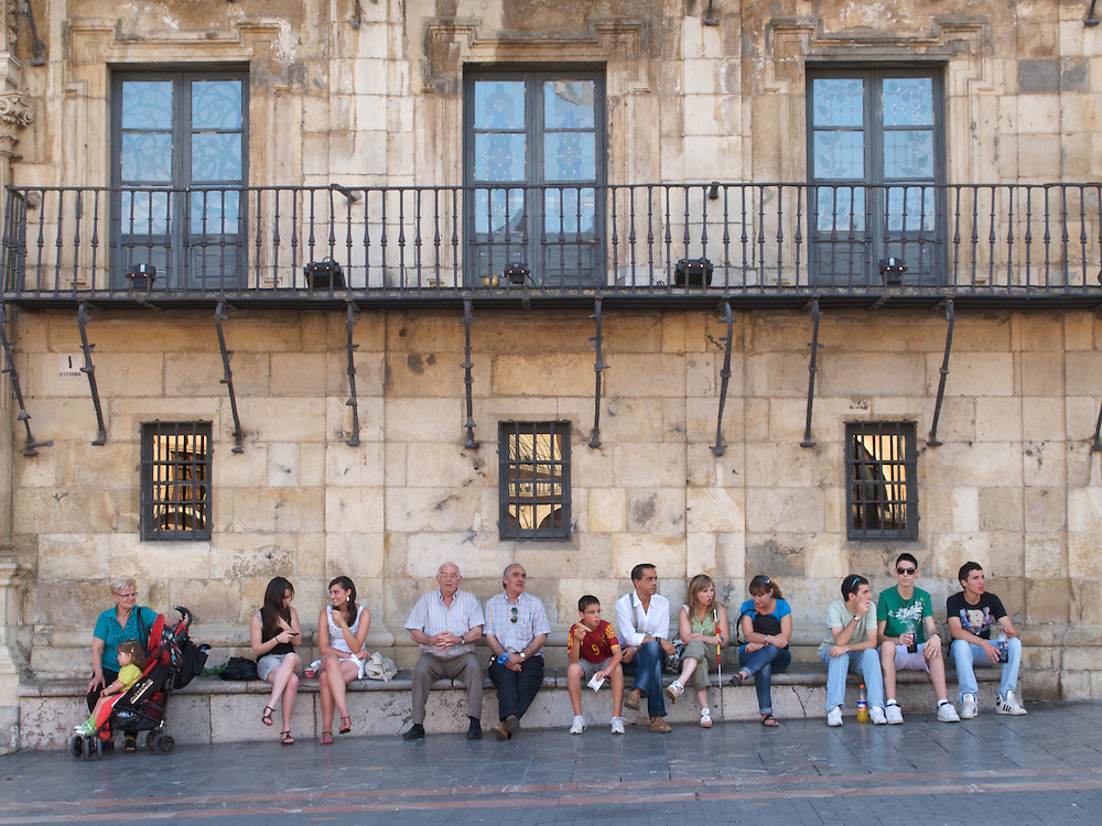 An assorted group of local residence sit in the warm evening air in the centre of Leon, North Spain. It is a scene repeated throughout Spain as the locals enjoy the evening air and activity.