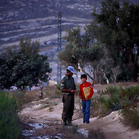 A Fijian member of the UNIFIL tropps in southern Lebanon talks with a local boy along a rugged road. Relations between the Fijian troops and the local populace were excellent when this photo was taken in 1981.