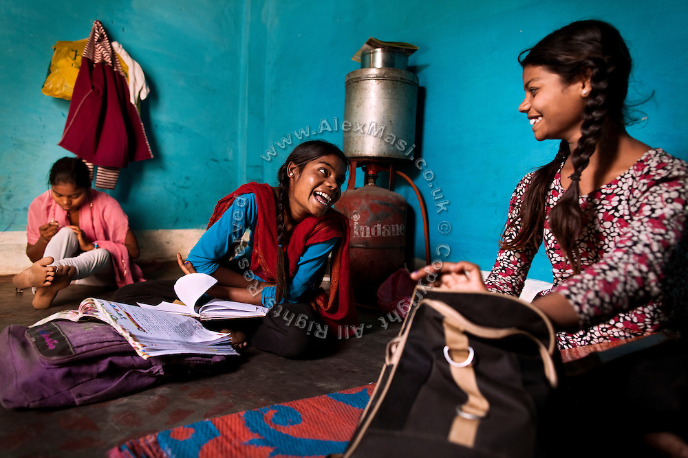 Jyoti, 13, (centre) is laughing with her sister Poonam, 12, (right) while completing their homework as their older sister Arti, 18, is applying nail polish, (left) sitting on the floor of their newly built home in Oriya Basti, one of the water-contaminated colonies of Bhopal, central India, near the abandoned Union Carbide (now DOW Chemical) industrial complex, site of the infamous '1984 Gas Disaster'. The two girls are studying in Year 6, out of 12, in 2015-16.