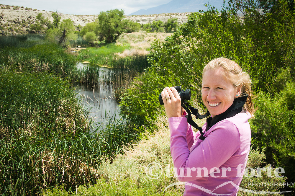 Portrait of a woman while she bird watches and looks through binoculars in marsh area of Owens River, Eastern Sierras, California.