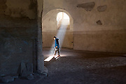 ROME - A visitor at the circis Maxentius along the Appian way steps into a ray of sunlight. Construction of the Appian way started in 312 BC and it was one of the earliest and strategically most important roads of Roman empire, connecting Rome to Brindisi. COPYRIGHT JURRIAAN BROBBEL