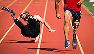 Stefan Leroy, left, Army, falls during the 100 meter dash against Marcus Chischilly, right, from Marines, during the track competition at the 2015 Dept. of Defense Warrior Games held at Butler Stadium aboard Marine Base Quantico on Tuesday June 23, 2015. (Alan Lessig/Staff)