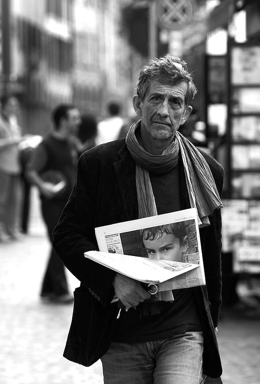 Man and boy in newspaper at Piazza Aldrovandi, Bologna.
