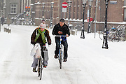 Met de volle tassen aan het stuur rijdt een meisje op de fiets door de sneeuw in Utrecht. Een jongen verstuurt ondertussen al fietsend een SMS.<br /> <br /> With bags full of shoppings a woman is cycling in the snow in Utrecht, while a man is sending text messages.
