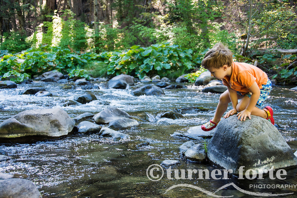 Toddler boy navigating over rocks in Deer Creek, California.
