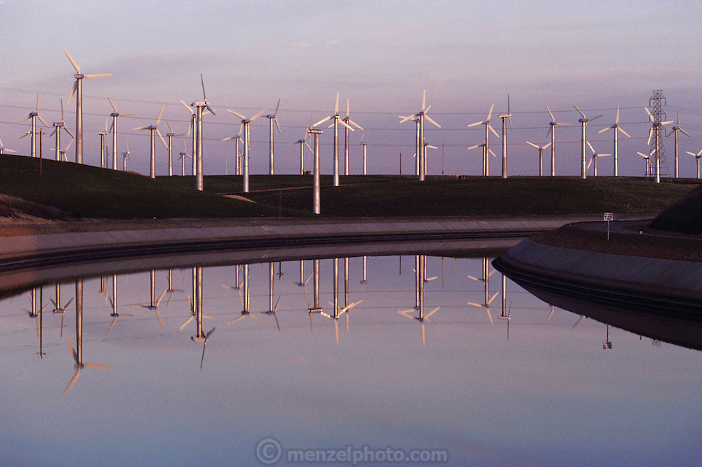 Wind farm producing electricity at Altamont, California. Wind Turbines. View of a wind farm with several wind turbines each with 3 spinning rotor blades. Wind power is used to drive a turbine for the generation of electricity. The electrical energy produced from a turbine is proportional to the cube of the wind speed. Thus, a 10-meter per second wind will produce 8 times more energy than a 5 meter per second wind. Wind turbines vary in size from large generators with a 1-3 megawatt capacity to small machines producing only a few kilowatts. (1985).
