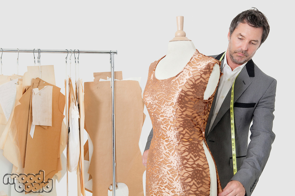Mature male tailor working on an outfit in design studio
