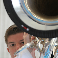 Mark Bates, 16, peers over his arm as he plays his tuba before the Tupelo High School Marching band leaves the band hall and completes their day of band camp outside Friday.