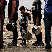 Syrian refugees fleeing the Turkish incursion in Rojava wait to receive water, bread and lentil soup as more than 200 arrive at the Bardarash IDP camp in Dohuk, Iraq onThursday, October 17, 2019. More than 1000 refugees have arrived in Northern Iraq since the beginning of the conflict, with many saying they paid to be smuggled through the Syrian border.