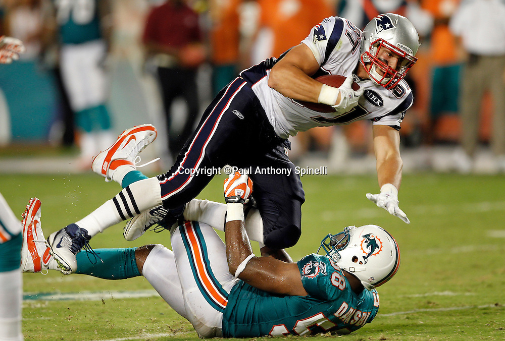 New England Patriots tight end Rob Gronkowski (87) gets some air as he catches a first down pass while getting tackled by Miami Dolphins linebacker Kevin Burnett (58) during the NFL week 1 football game against the Miami Dolphins on Monday, September 12, 2011 in Miami Gardens, Florida. The Patriots won the game 38-24. ©Paul Anthony Spinelli