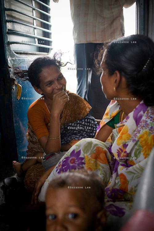 A begging singer from Andhra Pradesh, Shanti (left), chats with another beggar as they wait for the train to make a stop, when they will jump off and run to catch another train. They boarded the Himsagar Express 6318 at Ramgundam Stn. on 8th July 2009 and rode it for 3 stops as they sing and beg for change, disembarking at Vijayawada Junction.. .6318 / Himsagar Express, India's longest single train journey, spanning 3720 kms, going from the mountains (Hima) to the seas (Sagar), from Jammu and Kashmir state of the Indian Himalayas to Kanyakumari, which is the southern most tip of India...Photo by Suzanne Lee / for The National