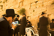 Orthodox Jewish man on his smart phone while praying at the Wailing Wall, Old City, Jerusalem