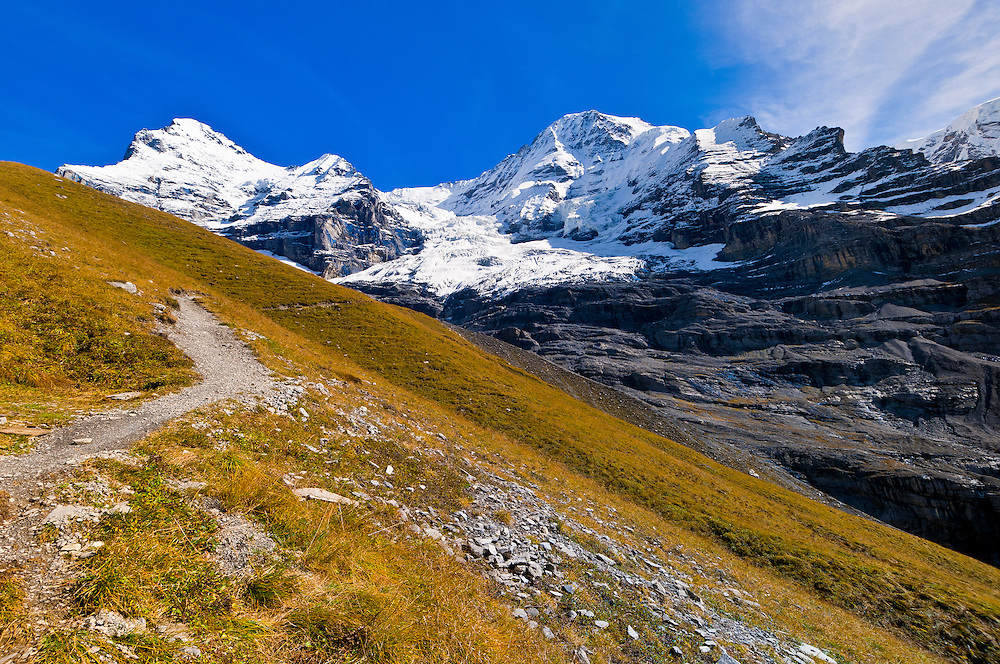 Hiking in the Swiss Alps from Eigergletscher down to Wengernalp (Eigergletscher in background), Kleine Scheidegg, Canton Bern, Switzerland