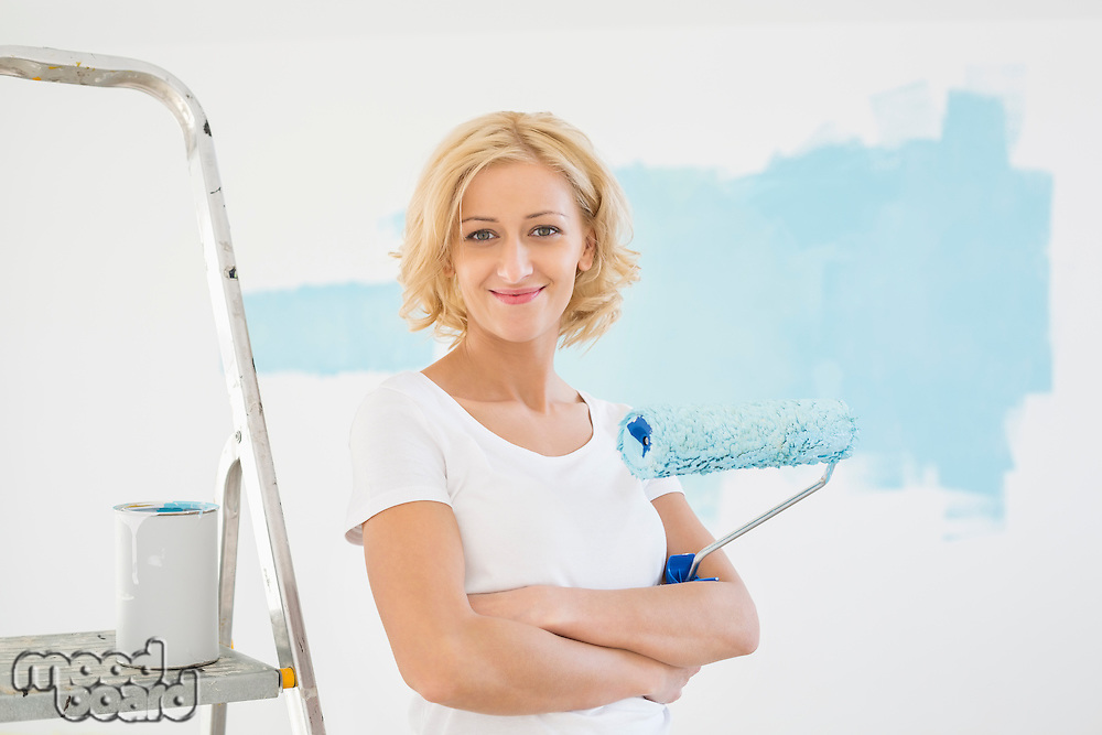 Portrait of woman with paint roller in new house