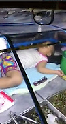 This adorable toddler found a strange place to take a nap - lying on the counter of her daddy's street food stall.<br /> <br /> The baby girl was stretched out on the chrome surface to the portable food wagon while fried  insects and vegetables were served up.<br /> <br /> Her father leans over her tiny legs to crack eggs before dropping them into a plastic bag to hand to a customer.<br /> <br /> Incredibly, the tot is oblivious to the world as music blares out, customers chat and cars drive by the roadside.<br /> <br /> The clip went viral after being shot by passerby Natchaporn Chansombun in the Arum Ammarin district of Bangkok, Thailand, on Tuesday night.<br /> <br /> She said: ''He loves his children so much he even takes them to work with him when he's selling food.<br /> <br /> ''I hope they love him a lot when they get older because he's working hard to take care of them.<br /> <br /> ''His wife was from Vietnam but she was selling food in a different area. <br /> <br /> There was nobody to look after the girl so he was babysitting her, and she was sleeping while he served food. It's better than leaving them with a babysitter.<br /> <br /> ''He can be the father and the mother at the same time. It was quite an inspiration to me.''<br /> © Natchaporn Chansombun/Exclusivepix Media
