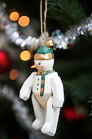 Snowman christmas decoration hanging from christmas tree close up