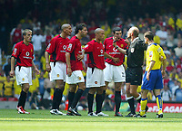 Photograph: Scott Heavey.<br />FA Community Shield fomr the Millenium Stadium in Cardiff. 10/08/2003.<br />The Man Utd team gather around referee Steve Bennett after Francis Jeffers kicked out on Phil Neville.