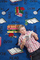 School boy reading book on floor in library