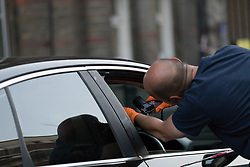 © Licensed to London News Pictures. 25/07/2017. LONDON, UK.  Police officers examine a car at the crime scene cordon on Burnham Road just off Roman Street this evening near Singh supermarket.  Two males in their late teens have been taken to hospital for treatment after an unknown liquid was thrown at them. Photo credit: Vickie Flores/LNP