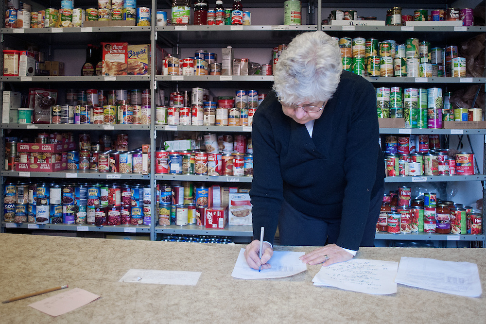 Nancy Bain, coordinator of the St. Vincents food pantry fill out paper work after the Alpha Beta Psi food drive on February 23rd, 2012.Photo by: Ross Brinkerhoff.