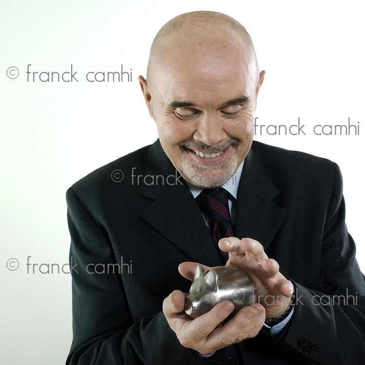 studio portrait isolated on white background of a man senior hoding a piggy bank