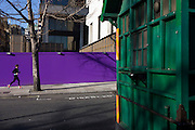 Lone woman jogger runs past purple construction hoarding and green taxi drivers' shelter.