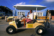 Local taxi driver uses a golf cart to transport tourists on the sandy roads of Isla de Holbox, Mexico.