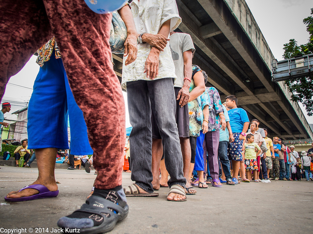 """07 AUGUST 2014 - BANGKOK, THAILAND:  People line up in the street before food distribution started at Pek Leng Keng Mangkorn Khiew Shrine. Thousands of people lined up for food distribution at the Pek Leng Keng Mangkorn Khiew Shrine in the Khlong Toei section of Bangkok Thursday. Khlong Toei is one of the poorest sections of Bangkok. The seventh month of the Chinese Lunar calendar is called """"Ghost Month"""" during which ghosts and spirits, including those of the deceased ancestors, come out from the lower realm. It is common for Chinese people to make merit during the month by burning """"hell money"""" and presenting food to the ghosts. At Chinese temples in Thailand, it is also customary to give food to the poorer people in the community.       PHOTO BY JACK KURTZ"""