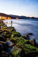 Silhueta de homem pescando na Praia da Armação ao anoitecer. Florianópolis, Santa Catarina, Brasil. / Silhouette of a man fishing at Armacao Beach at dusk. Florianopolis, Santa Catarina, Brazil.