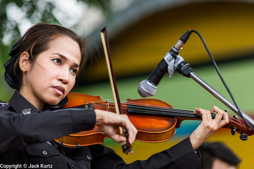 """15 JUNE 2014 - BANGKOK, THAILAND: A Thai policewoman plays violin on a stage during a """"Return Happiness to Thais"""" party in Lumpini Park in Bangkok. The Thai military junta, formally called the National Council for Peace and Order (NCPO), is sponsoring a series of events throughout Thailand to restore """"Happiness to Thais."""" The events feature live music, dancing girls, military and police choirs, health screenings and free food.   PHOTO BY JACK KURTZ"""