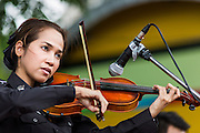 "15 JUNE 2014 - BANGKOK, THAILAND: A Thai policewoman plays violin on a stage during a ""Return Happiness to Thais"" party in Lumpini Park in Bangkok. The Thai military junta, formally called the National Council for Peace and Order (NCPO), is sponsoring a series of events throughout Thailand to restore ""Happiness to Thais."" The events feature live music, dancing girls, military and police choirs, health screenings and free food.   PHOTO BY JACK KURTZ"