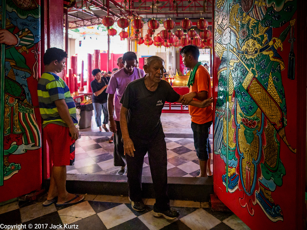 04 SEPTEMBER 2017 - BANGKOK, THAILAND: A man prays as he walks into Chaomae Thapthim Shrine for a food distribution. About 1,000 people came to the shrine for the annual food distribution. Staples, like rice and cooking oil, are donated to the shrine throughout the year and donated to poor people from the communities around the shrine. Food distributions like this are a tradition at Chinese shrines in Bangkok and a common way of making merit for the people who donate the staples.     PHOTO BY JACK KURTZ