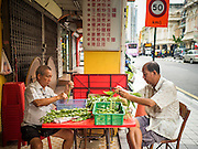 06 JUNE 2015 - KUALA LUMPUR, MALAYSIA: Men clean vegetables at a Chinese street food shop in Kuala Lumpur.    PHOTO BY JACK KURTZ