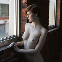 A nude lady, gazing out of a window, in a brick building