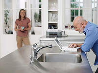 Man using laptop by kitchen sink woman watching from distance