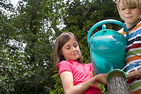 Boy and girl (7-9) watering garden together