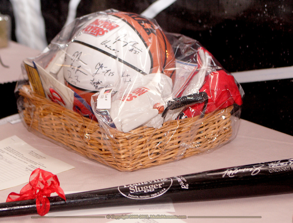 Two of the many items available in the silent auction are this basket including a ball signed by team members, dinner and U.D. Flyer tickets and merchandise; and a Cincinnati Reds bat autographed by Ken Griffey Jr.
