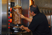 Man carving slices of Shawarma a large skewer of lamb, chicken, turkey or beef meat and llamb fat. is a very popular street food in Israel and the middle east