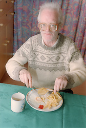 Portrait of elderly man eating meal in Salvation Army hostel,