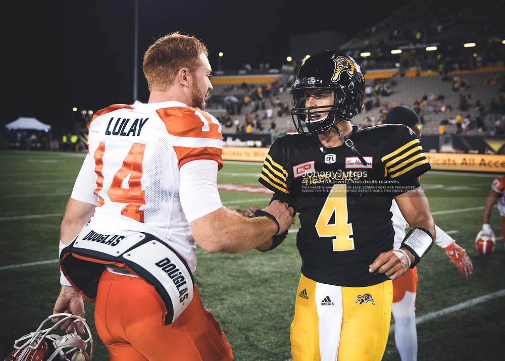 Travis Lulay (14) of the BC Lions and Zach Collaros (4) of the Hamilton Tiger-Cats after the game at Tim Hortons Field in Hamilton, ON., on Saturday, July 15, 2017. (Photo: Johany Jutras)
