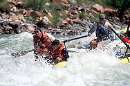 Jeff Pyle, right, manuvers his boat through Upset Rapid on the Colorado River.  In the front of the boat Arturo(top), Sonia(middle), and James (bottom), Weiss hold on.