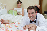 Bride and groom relaxing among presents, focus on groom