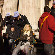 Police moving in to re-capture the steps to the cathedral. The woman knows the police is about to tip her off her chair and down the steps.The London Stock Exchange was attempted occypied in solidarity with Occupy Wall in Street in New York and in protest againts the economic climate, blamed by many on the banks. Police managed to keep people away fro the Patornoster Sqaure and the Stcok Exchange and thousands of protestors stayid in St. Paul's Square, outside St Paul's Cathedral. Many camped getting ready to spend the night in the square.