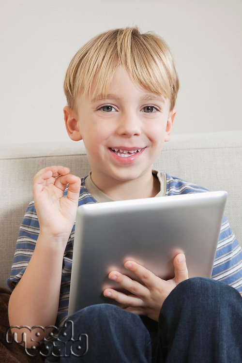 Young boy with digital tablet gesturing OK